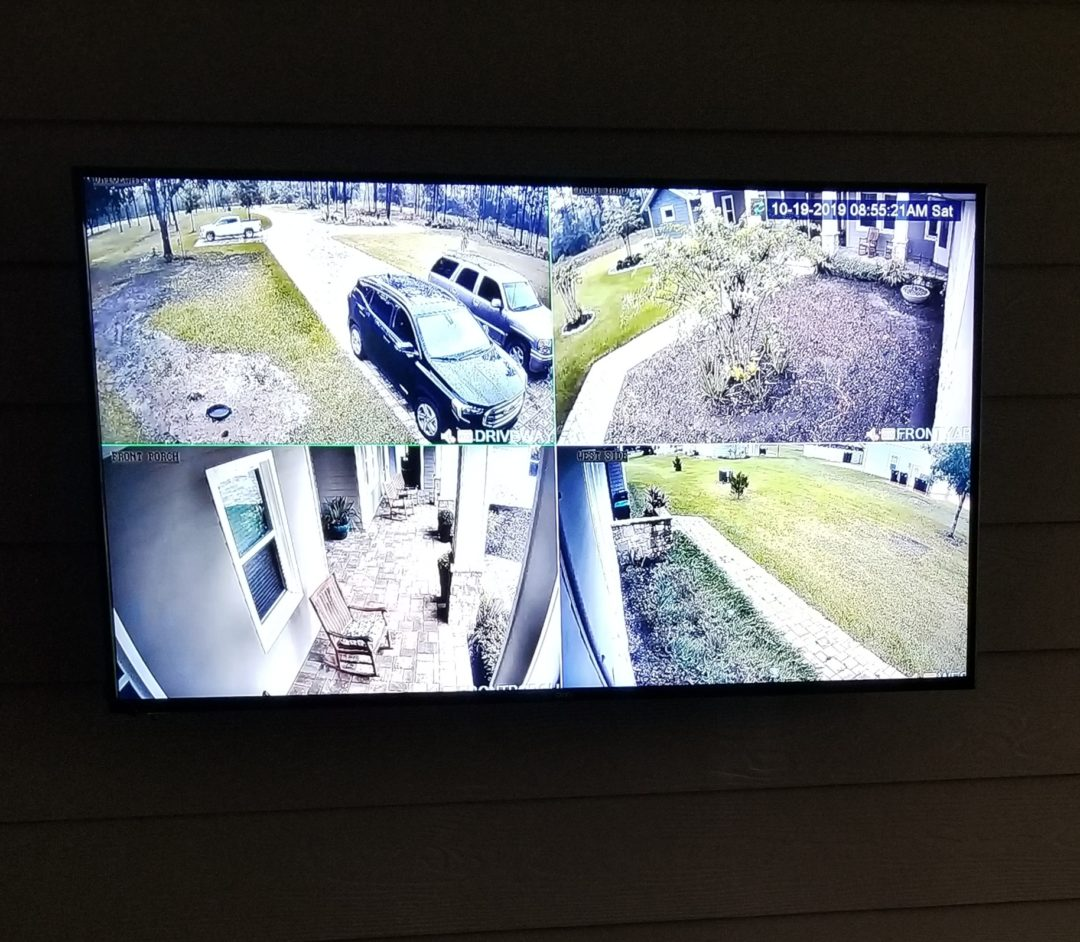 Photo of outdoor wall mounted TV with 4 tile live security feed installed by Dream Controls and Design