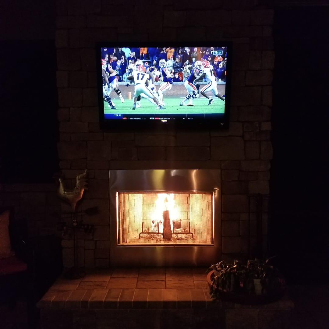 Photo of Outdoor fireplace mounted TV by Dream Controls and Design